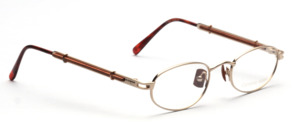 Metal frame in matt gold with wooden nose pads and elaborately designed temples with wooden inlay