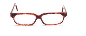 Flache, handgefertigte Brillenfassung in verschiedenen Brauntönen gemustert und mit Goldenen und Pinken Farbakzenten