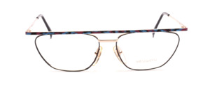 Designer frame in gold with a black glass rim and a colorful patterned upper edge and straps