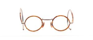Kinderbrille aus den 1920er Jahren in Rund mit Hellbraun gemustertem Windsorrand und halb überzogenen Gespinstbügeln in 145 mm Länge